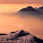 Agosto 2014 - Tramonto invernale dipinto di rosa sulla Pianura Padana, visto dalla cresta meridionale del Monte Baldo. Uno strato di nebbia avvolge la Pianura, e si infila anche nelle vallate del bresciano e sul Lago di Garda. Le vette più alte si ergono verso il cielo come fossero isole in un candido mare.