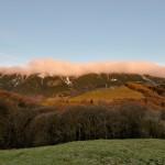 Novembre 2014 - Nella bellissima foto di Diego Bortignon, scatta il 23 novembre alle ore 07:30 da Novezzina, vediamo che le cime del versante orientale del Monte Baldo sono ricoperte da uno strano strato nuvoloso. Si tratta di banner clouds, nubi orografiche che si formano sottovento alla cresta principale di una catena montuosa quando il vento è perpendicolare ad essa. Il vento occidentale presente in quota quel giorno, infatti, ha provocato una zona di turbolenza ad est del Baldo (rotore) causando una regione di sollevamento proprio subito sotto alle cime del Baldo. L'umidità presente all'interno di tale zona di correnti ascendenti condensando ha dato origine alla nube.