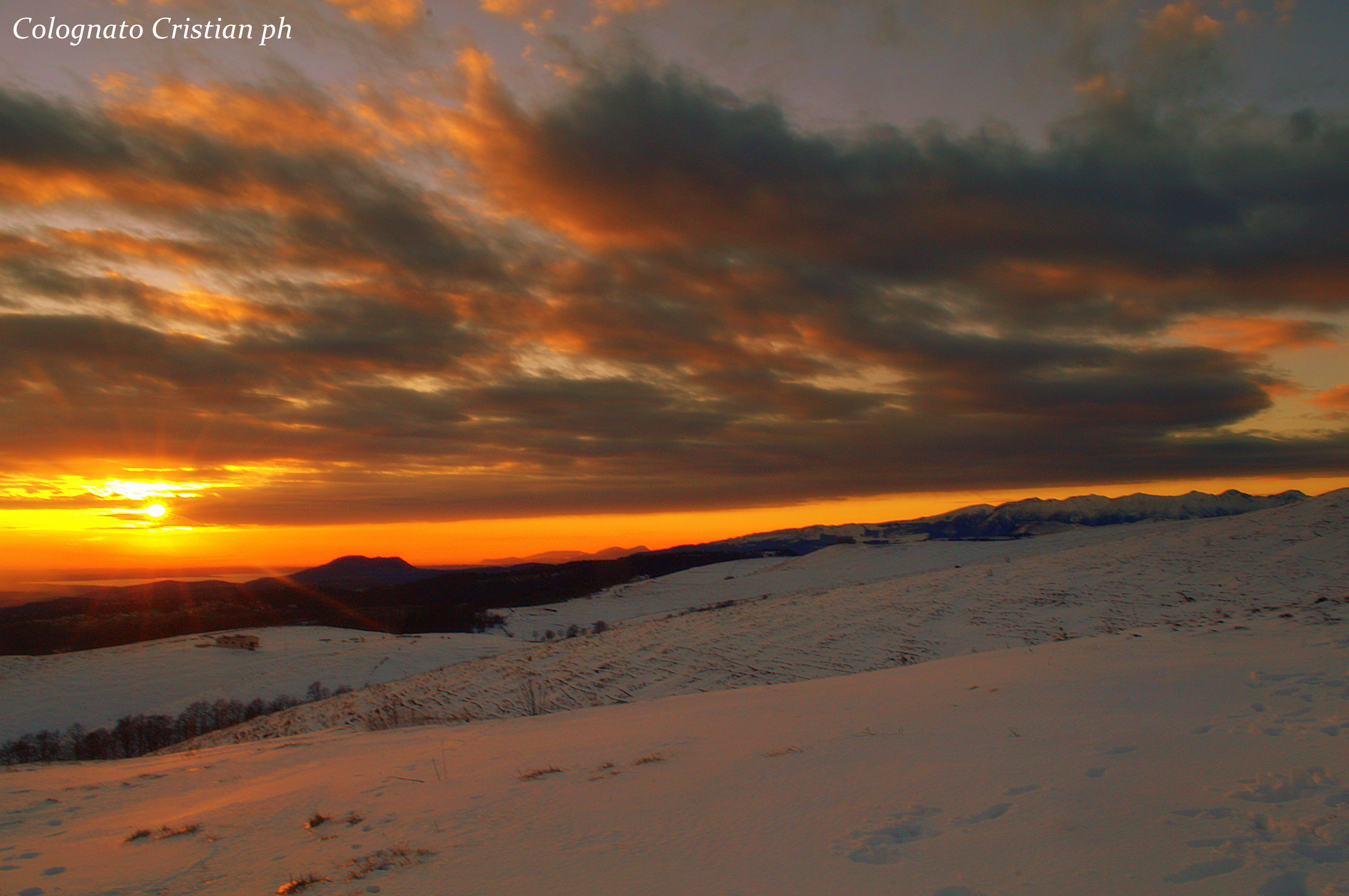 Gennaio 2015 - Nella foto di Cristian Colognato, il tramonto del 25 gennaio da San Giorgio verso Sud-Ovest. Il sole illumina il basso Lago di Garda e l'altipiano della Lessinia, facendosi spazio tra strati nuvolosi. il Monte Baldo, a destra nell'immagine, resta a guardare.