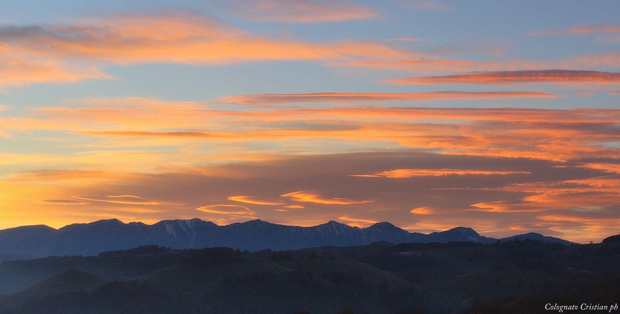 Ottobre 2015 - Per il mese di ottobre vi proponiamo uno scatto in cui vediamo nubi lenticolari e cirrostrati sul Monte Baldo al tramonto (foto Colognato). Le nubi lenticolari, dette anche lee-clouds, si formano tipicamente sottovento alle Alpi con correnti settentrionali o nord-occidentali in alta quota.